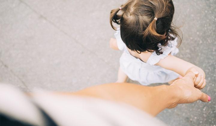 Toddler girl walking holding mother's hand
