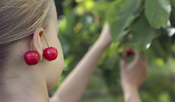 Girl picking fruit and wearing cherries as earrings