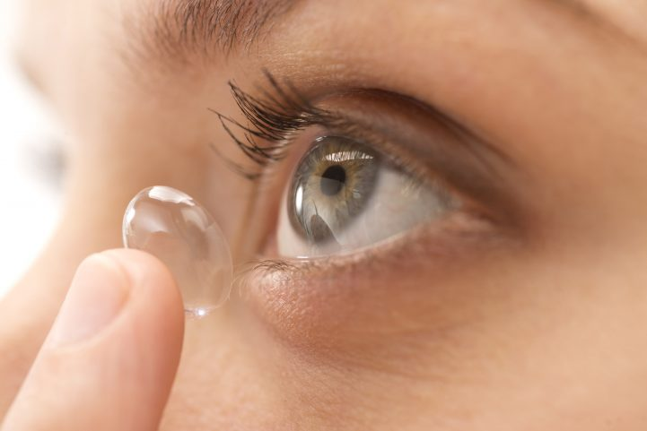 Young woman putting in contact lens, close-up
